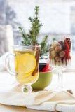 Tè verde caldo fresco in tazza di vetro con il limone e cannella, dolci di cioccolato merce nel carrello e dadi e cannella Fotografia Stock