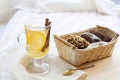 Tè verde caldo fresco in tazza di vetro con il limone e cannella, dolci di cioccolato merce nel carrello e dadi e cannella Immagine Stock Libera da Diritti