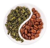 Tè verde del foglio contro i chicchi di caffè in Yin Yang fotografia stock