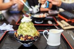 Tè verde di Bingsu con il fagiolo rosso dolce sulla tazza nera e sul vassoio nero Fotografia Stock