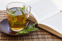 Tè verde e foglie della menta in una tazza di vetro con un libro Immagini Stock