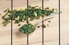 Tè verde in un cucchiaio del ferro su di legno Immagine Stock