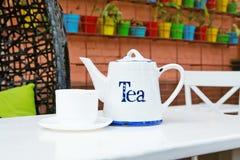 Té blanco de la taza y de la tetera en cafee al aire libre Fotografía de archivo