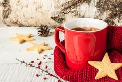 Té caliente del invierno en una taza roja con las galletas de la Navidad Fotografía de archivo libre de regalías