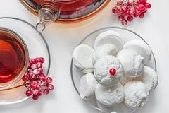 Té caliente en la Navidad en la taza transparente de cristal con el árbol del té y tortas en la forma de los muñecos de nieve fue Imagenes de archivo