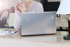 Té caliente en la oficina en la madrugada, una taza en manos Fotografía de archivo libre de regalías