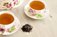 Té candente del hibisco en una taza de cristal en una tabla de madera entre los pétalos color de rosa y las natillas secas del té Fotos de archivo libres de regalías