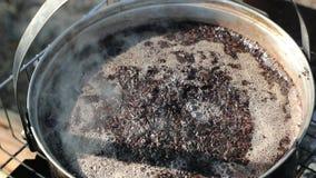 Té cocinado de Puer en un cazo grande sobre un fuego almacen de metraje de vídeo
