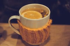 Té con el jengibre y el limón en taza hecha punto en café imagen de archivo