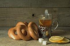 Té con el limón en soporte de vaso en la tabla de madera vieja Foto de archivo libre de regalías