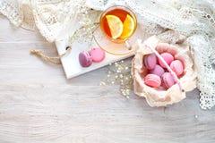 Té con el limón, las flores salvajes y el macaron en la tabla de madera blanca Imagen de archivo libre de regalías