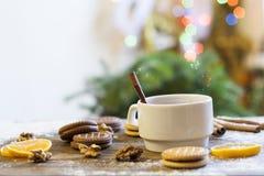 Té con el limón, las mandarinas, las galletas y las nueces en la decoración de la Navidad con el árbol de navidad, las nueces y l Foto de archivo libre de regalías