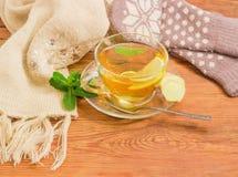 Té con el limón, menta, jengibre contra de las manoplas de lana, bufanda Foto de archivo libre de regalías