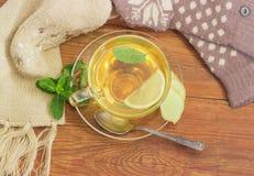 Té con el limón, menta, jengibre por otra parte de las manoplas de lana, bufanda Imagenes de archivo