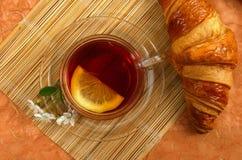 Té con el limón y el croissant Foto de archivo libre de regalías