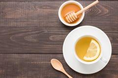 Té con el limón y la miel en el fondo de madera Foto de archivo