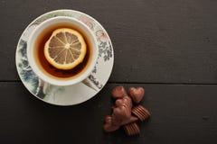 Té con el limón y los dulces Foto de archivo