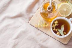 Té con el tilo, la miel y el limón La bandeja en la cama, el concepto del tratamiento de fríos Imagen de archivo libre de regalías