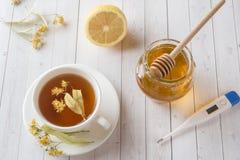 Té con el tilo, la miel y el limón Comida sana, tratamiento del termómetro de los fríos en la tabla Fotos de archivo