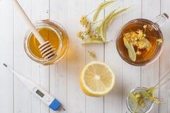 Té con el tilo, la miel y el limón Comida sana, tratamiento del termómetro de los fríos en la tabla Foto de archivo libre de regalías