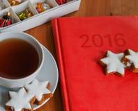 Té con la torta, el diario y la decoración de la Navidad Fotos de archivo libres de regalías