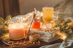 Té con las bayas espino amarillas y el jengibre en ramas de los libros viejos, de la miel, de la vela y de la conífera La atmósfe imagen de archivo