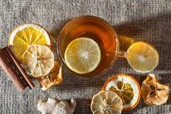 Té con las especias, miel, canela, limón del jengibre en un fondo de lino foto de archivo libre de regalías