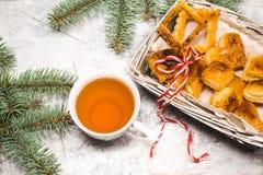 Té con las galletas del gingebread por la tarde de la Navidad Ahueque cerca de rama spruce en el copyspace de madera blanco de la Foto de archivo libre de regalías