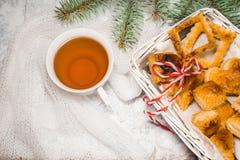 Té con las galletas del gingebread por la tarde de la Navidad Ahueque cerca de rama spruce en el copyspace de madera blanco de la Imágenes de archivo libres de regalías
