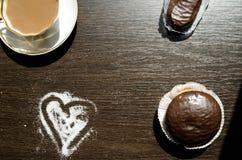 Té con leche en un  blanco de la porcelana Ñ ascendente y tortas de chocolate Imagenes de archivo