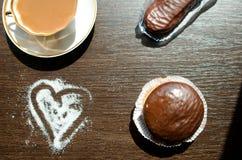 Té con leche en un  blanco de la porcelana Ñ ascendente y tortas de chocolate Imagen de archivo libre de regalías