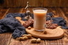 Té con leche y galletas en la taza de cristal en un tablero hermoso Todavía vida con té, galletas, nueces y una nuez antigua Imágenes de archivo libres de regalías
