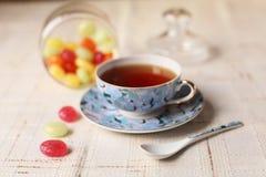 Té con los caramelos de azúcar coloreados Foto de archivo