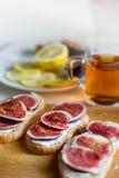 Té con los snaks con los higos y el queso cremoso en el fondo blanco de la materia textil Foto de archivo