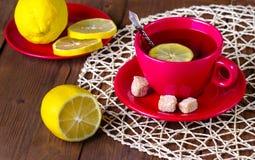 Té con un limón en una taza roja Foto de archivo
