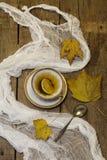 Té con un limón y las hojas de otoño en una tabla de madera Fotos de archivo libres de regalías