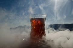 Té de Azerbaijan del turco en fondo al aire libre tradicional de la naturaleza del glasse y del pote con luz del sol y humo Conce Fotos de archivo libres de regalías