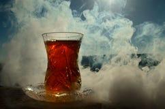 Té de Azerbaijan del turco en fondo al aire libre tradicional de la naturaleza del glasse y del pote con luz del sol y humo Conce Imagen de archivo libre de regalías