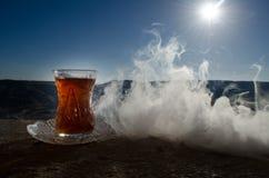 Té de Azerbaijan del turco en fondo al aire libre tradicional de la naturaleza del glasse y del pote con luz del sol y humo Conce Fotografía de archivo libre de regalías