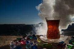Té de Azerbaijan del turco en fondo al aire libre tradicional de la naturaleza del glasse y del pote con luz del sol y humo Conce Imagen de archivo