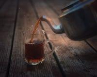 Té de colada antiguo de la caldera de té en una taza de cristal Fotografía de archivo