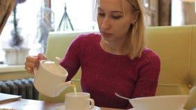 Té de colada de la mujer bastante rubia de los jóvenes en la taza blanca, interior del café almacen de video