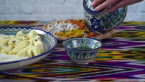 Té de colada de la mujer de la tetera de cerámica del uzbek tradicional, vídeo del hd almacen de metraje de vídeo