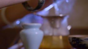 Té de colada de la infusión del amo del primer de gaiwan en cuenco de la imparcialidad en la ceremonia de té almacen de metraje de vídeo