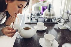 Té de colada de la mujer en la taza de cerámica en la tabla imagen de archivo