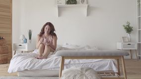 Té de consumición atractivo o café de la mujer adulta que se sienta en cama por la mañana Señora sonriente que se relaja en casa  almacen de video
