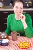 Té de consumición de la chica joven en la cocina Fotos de archivo