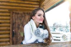 Té de consumición de la chica joven linda en cabaña Imagen de archivo libre de regalías