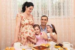 Té de consumición de la familia en el comedor, mujer embarazada foto de archivo libre de regalías