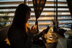 Té de consumición de la mujer en café y el trabajo imagen de archivo